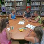 Dzieci siedzą wokół stołu i wykonują prace z plasteliny