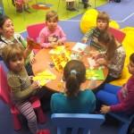Dzieci siedzą wokól stolik i wycinają i naklejają