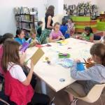 Dzieci przy stole wykonują laurki