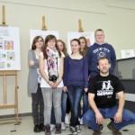 Młodzież z nauczycielem pośród swoich prac