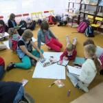 Dzieci rysują na dużym arkuszu papieru ułożonym na podłodze