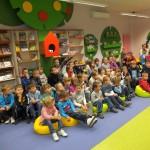 Dzieci siedzą i słuchają prowadzącej, kilkoro zgłasza się do odpowiedzi