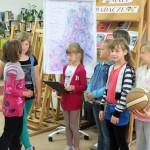 Dzieci prezentują swój rysunek na sztaludze