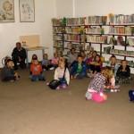 Dzieci siedzą na podłodze i słuchają bibliootekarkę