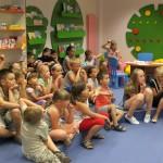 Dzieci siedzą i słuchają osobę prowadzącą zajęcia