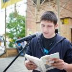 Młodzieniec czyta książkę przed mikrofonem