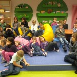 Dzieci siedzą i słuchają wypowiedzi prowadzącej