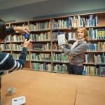 Gość trzyma książke na tle regałów, inna osoba robi jej zdjęcie telefonem