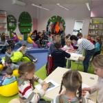 Dzieci w grupkach przyklejają obrazki do kartki, bibliotekarz im pomaga