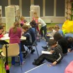 Dzieci siedząc przy stolikach i na podłodze na kolanach wykonują rysunki