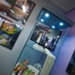 Plansze wystawy oraz gablota z książkami o fotografii i monitorem z pokazem zdjęć