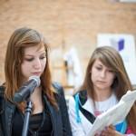 Dwie dziewczyny czytają książkę przy mikrofonie