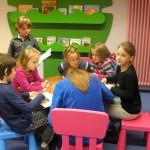 Dzieci siedzą wokół stolika i rysują