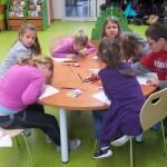 Dzieci siedzą wokół stołu i rysują