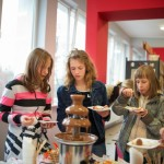 Trzy dziewczyny spożywają przy stole z poczęstunkiem