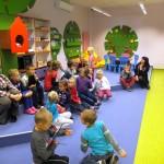 Dzieci z wychowawczyniami siedzą i słuchają prowadzącej