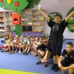 Dzieci siedzą na schodku, jeden chłopiec wstał i ponosi ręce do góry