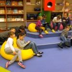 Dzieci siedzą na pufach i rysują
