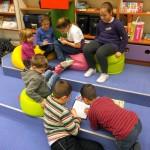 Dzieci rysują siedząn na pufach i na podłodze
