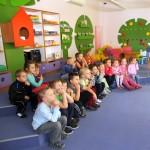 Dzieci siedzą i oglądają prezentację na ekranie