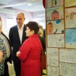 Goście w Oddziale dla Dzieci stoją przy wystawie rysunków