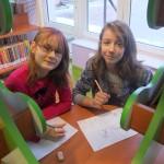 Dwie dziewczynki siedzą przy stole ze swoimi rysunkami i patrzą w obiektyw