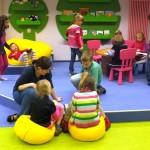 Troje dzieci ipracownik biblioteki oglądają swoje prace plastyczne