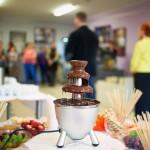 Fontanna gorącej czekolady na stole, w tle autorzy i zgromadzeni goście