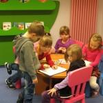 Dzieci przy stoliku rysują i oglądają czasopisma