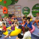 Dzieci siedzą na podłodzie lub na pufach i słuchają prowadzącą
