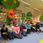 Dzieci siedzą i słuchają prowadzącej