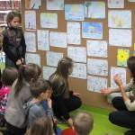 Dzieci oglądają na ścianie wystawę rysunków