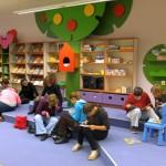 Dzieci w grupkach oglądają ksiżki