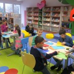 Dzieci przy stolikach wycinają i wyklejają