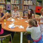 Dzieci siedzą wokół stołu zajmując się wycinaniem i klejeniem