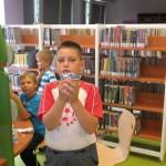 Chłopiec pokazuje wycięty z papieru samochodzik