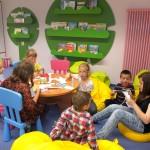 Dzieci przy stoliku wycinają i kleją elementy z papieru