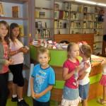 Sześcioro dzieci stoi przy ladzie bibliotecznej