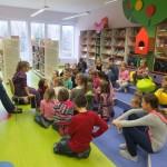 Dzieci siedzą na podłodze i słuchają prowadzącą zajęcia