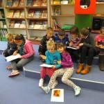 Dzieci w grupkach piszą na kartkach