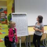 Bibliotekarz na flipcharcie przygotował tekst listu do butelki, dziewczynka odczytuje go przez mikrofon