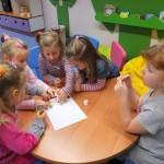 Pięć dziewczynek siedzi wokół stolika i przyklejają obrazki do kartki