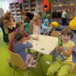 Dzieci siedzą przy stole i ozdabiają butelki naklejkami