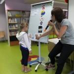 Dziewczynka na flipcharcie wykonuje zadanie przygotowane przez bibliotekarza