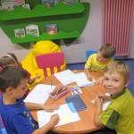 Czwórka dzieci siedzi przy stoliczku i rysuje