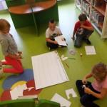Dzieci siedzą na podłodze i na dużym arkuszu papieru przygotowują grę planszową