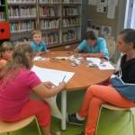 Dzieci siedzą wokół stołu i piszą lub rysują
