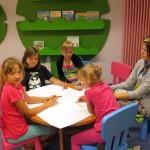 Dzieci siedzą wokół stolika i rysują na dużym arkuszu papieru