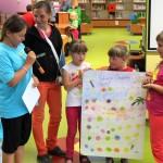 Dzieci trzymają plaszę ze swoją grą i opisują ją innym kolegom