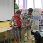 Gość zakłada dziewczynce kamizelkę ratunkową